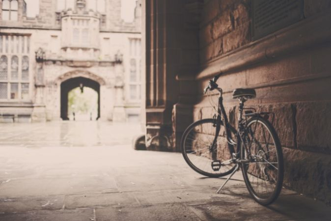 Bicycle parked against a wall at university