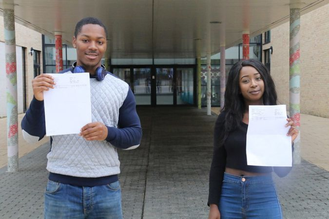 2 students holding up their exam results