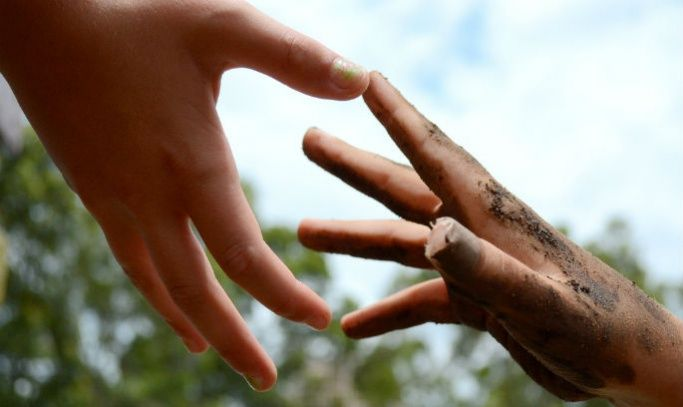 Two hands touching to symbolise making a difference