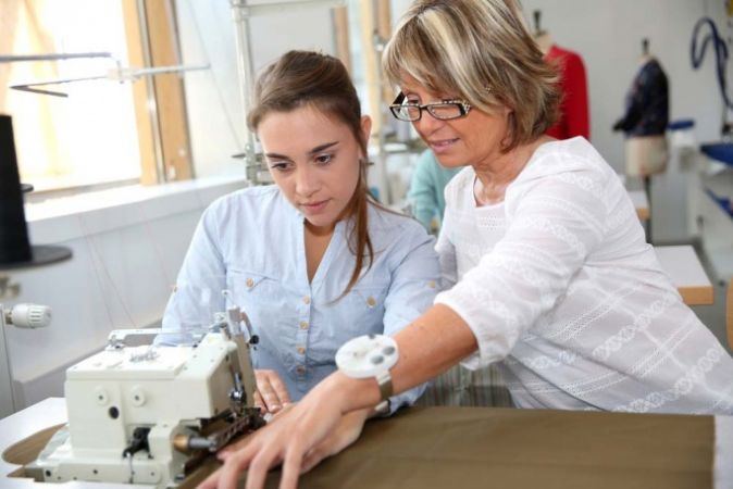 Teacher showing student how to work sewing machine to help her get the most out of work experience