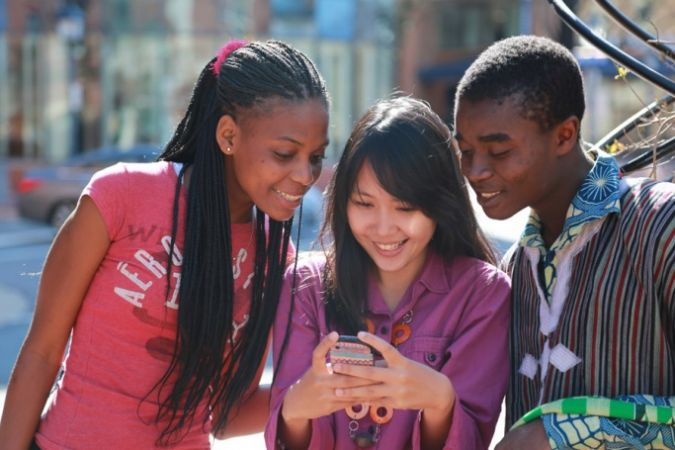 three students looking at a mobile phone