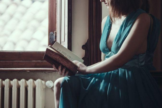 Woman reading by a window wearing a dress