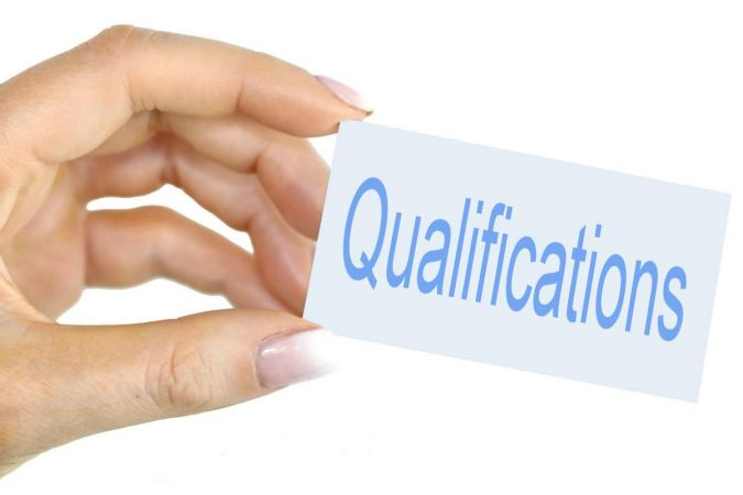"""Someone holding a card saying """"qualifications"""""""