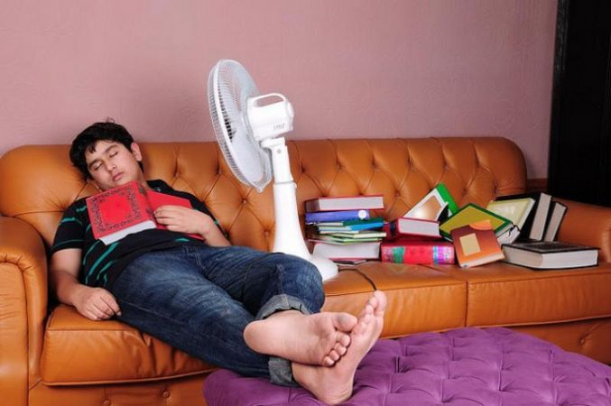 student sleeping amongst books