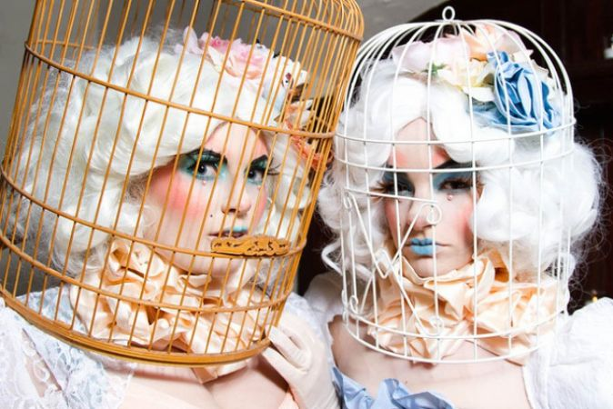 Two women wearing birdcages