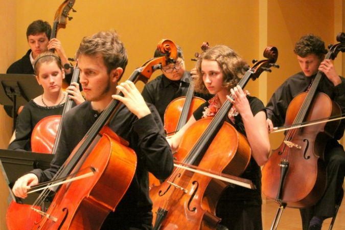 a student orchestra playing string instruments