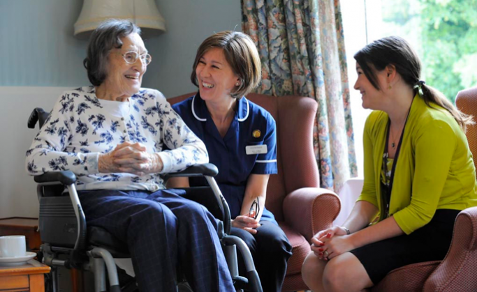 An older person being laughing with a nurse and care worker