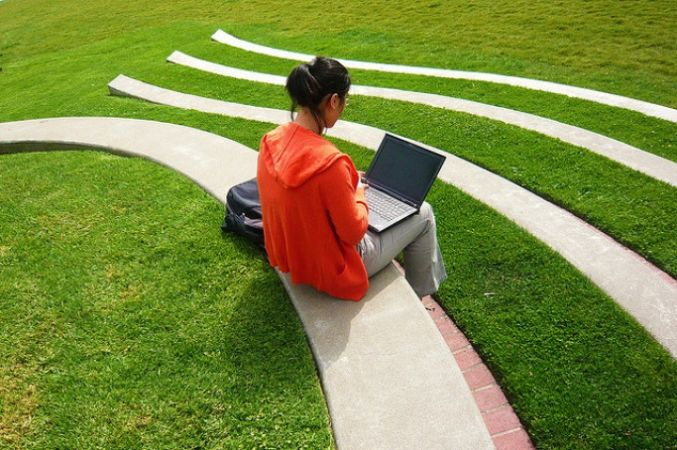 student with laptop sitting outside