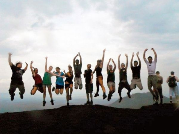 group of students jumping at the top of a mountain