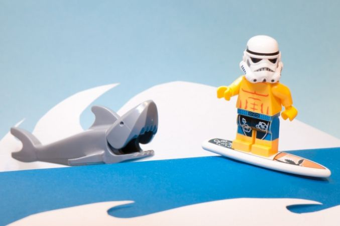 Lego stormtrooper surfing away from a shark