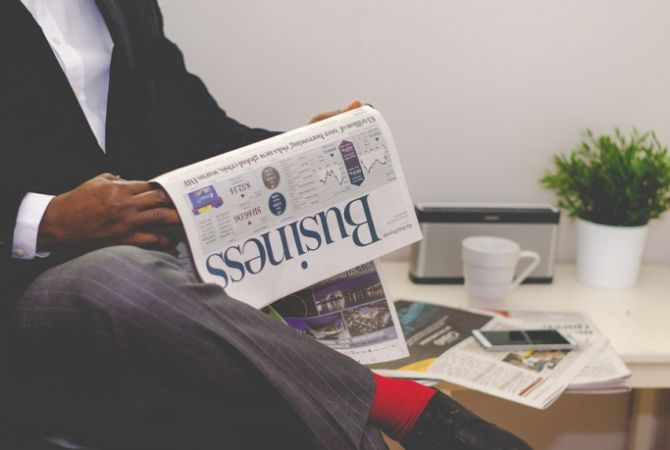 Man in improving his commercial awareness skills by reading a business newspaper