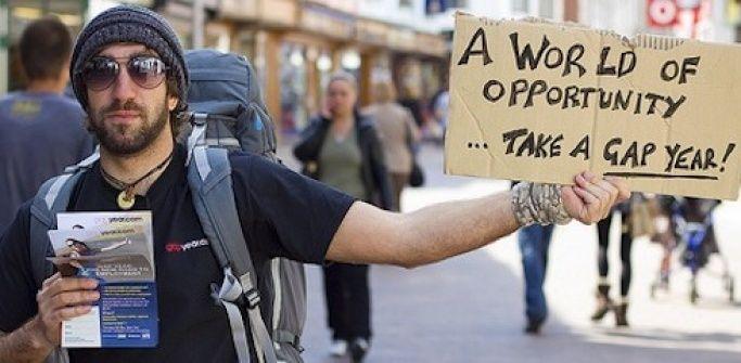 Traveller with backpack holding cardboard sign