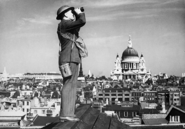 Man standing on a rooftop with binoculars