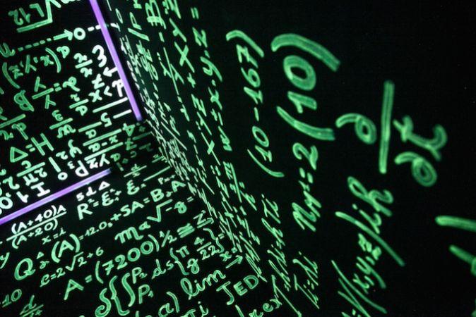 physics equations written on a dark wall