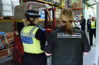 A police officer and UK border agent in a warehouse