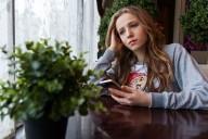 Teenage girl sad with phone