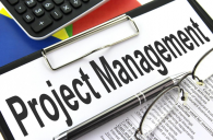 """A clipboard with a piece of paper saying """"project management"""""""