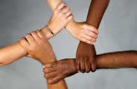 4 people holding each other's wrists in a circle